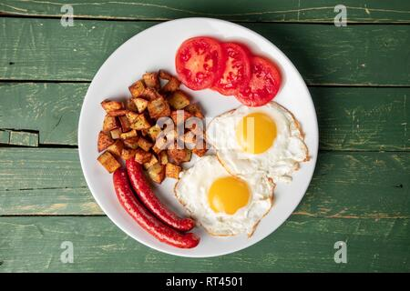 Baked sausage with eggs and potato on a green wooden background - Stock Photo