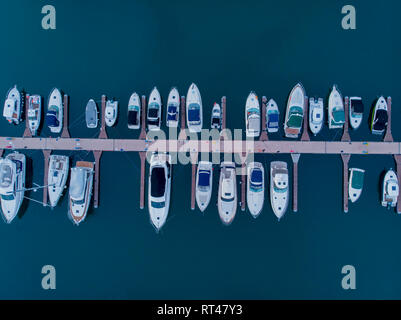 Aerial top down picture of marina a dock basin with moorings and supplies for yachts and small boats showing the floating dock walkway supported by po - Stock Photo