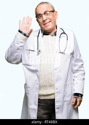 Handsome senior doctor man wearing medical coat Waiving saying hello happy and smiling, friendly welcome gesture - Stock Photo