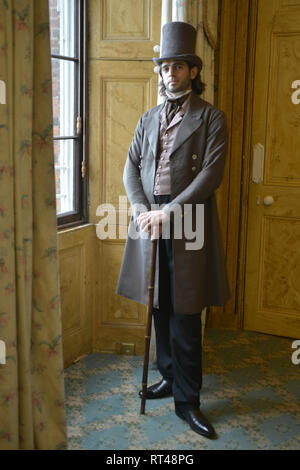 A handsome young Victorian man in a historically accurate suit stands against a wallpaper backdrop for a portrait- he has a top hat and cane - Stock Photo