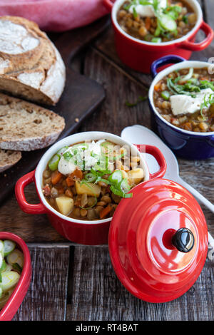 Savoury lentil soup with sour cream and fresh bread - Stock Photo