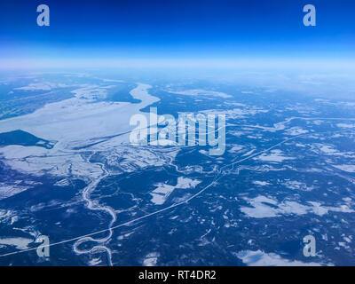 An aerial view from the airplane flying high above the ground. A look from the plane´s window. There is the frozen Lake Laduga down below. - Stock Photo