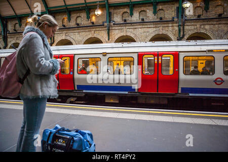 Waiting on Notting Hill Gate tube station platform, London - Stock Photo