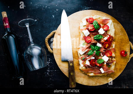 italian homemade flat bread with tomato, feta cheese, ham, and basilic, on  a round cutting board over a black board, flat lay with knife and red wine