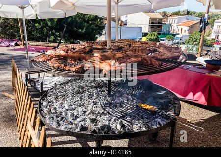 Assortment of grilled sausages and kebabs on big round grill in medieval fair - Stock Photo