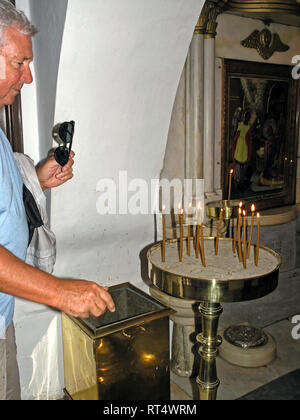 visitor lighting candle, Church of Annuciation, miraculous icon found,1833, Greek Orthodox, religious practise, pray, Hora, Cyclades, Tinos, Greece, E - Stock Photo