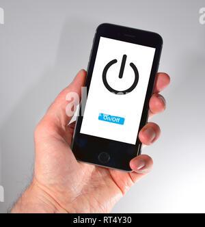 iPhone held in hand - power symbol - Stock Photo