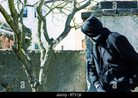 Unknown man in hood as robber or burglar or thief is spying around property with a plan to do illegal activity - Stock Photo