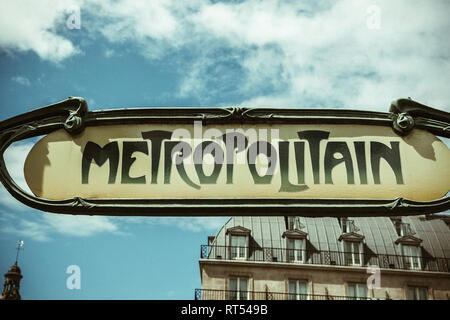 Art nouveau metropolitain sign in Paris, France ith traditional French real estate apartment building in the background  - Stock Photo