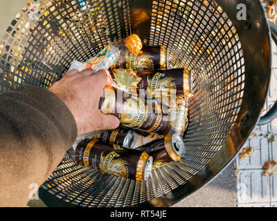 STRASBOURG, FRANCE - SEP 24, 2017: POV Male hand throwing taking Grimbergen beer aluminium can in a public waste bin - homeles concept - Stock Photo