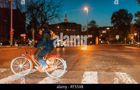 STRASBOURG; FRANCE - OCT 31; 2017: Young woman on red ike crossing street at night in front of the cars dusk sky in Strasbourg, Alsace  - Stock Photo