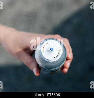 Woman holding aerosol bottle with canned compressed air in hand - view from above  - Stock Photo