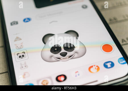 PARIS, FRANCE - NOV 9 2017: Panda bear 3d animoji emoji generated by Face ID facial recognition system with large smile face emotion close-up of the new iphone X 10 Display - tilt-shift lens used  - Stock Photo