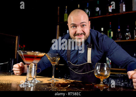 Portrait of angry and stressed barman with bowtie behind the bar with alcoholic drinks around. Stressful lifestyle of barista concept. - Stock Photo