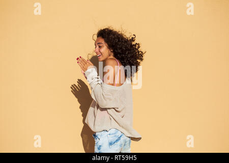 Portrait of teenage girl wearing pullover, orange wall - Stock Photo