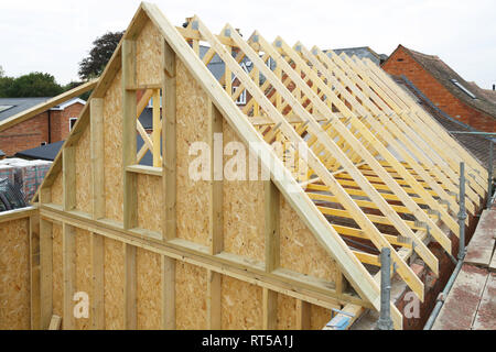 Gable and wooden roof trusses to a timber frame house under construction - Stock Photo