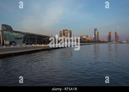 Baky skyline view from Baku boulevard the Caspian Sea embankment . Tall buildings in Baku. Ship cranes . Moon Baku Business Center - Stock Photo