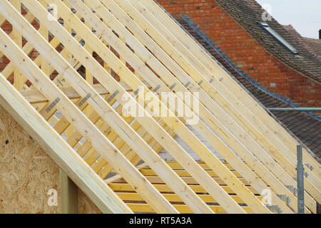 Detail of new timber roof trusses on a new roof being installed to a period house restoration in England - Stock Photo