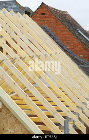 Detail of timber roof trusses on a new roof under construction - Stock Photo