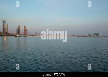 Baky skyline view from Baku boulevard the Caspian Sea embankment . Tall buildings in Baku. Ship cranes . Moon. harbor . Port - Stock Photo