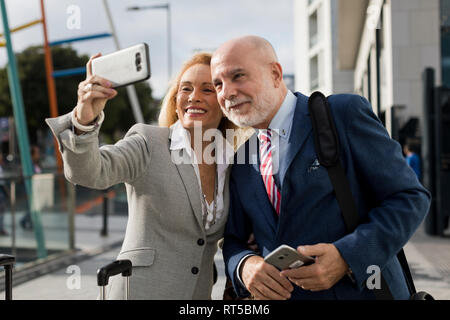 Senior businessman and businesswoman with baggage taking a selfie in the city - Stock Photo