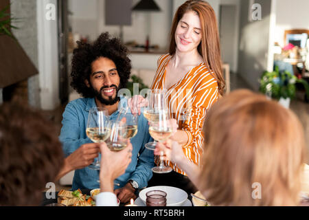Friends drinking wine at a dinner party, clinking glasses - Stock Photo