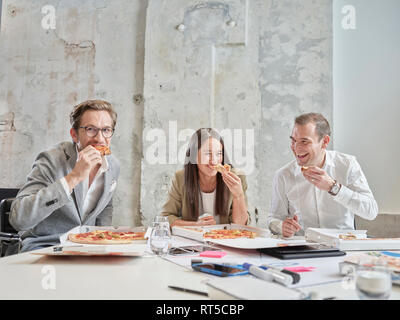 Happy colleagues having lunch break with pizza in conference room - Stock Photo
