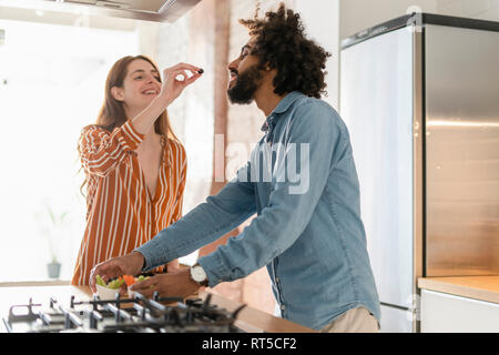 Couple standing in kitchen, preparing dinner party, woman feeding man with olive