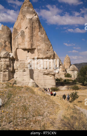 Tourists walking past a rock-cut cave dwelling with pigeon coops in the Valley of Love near Goreme, Cappadocia region,Turkey - Stock Photo