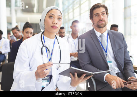 Female doctor with businessman attending seminar - Stock Photo
