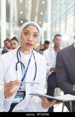 Female doctor with notebook and pen attending seminar - Stock Photo