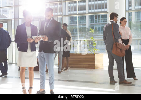 Diverse business people looking and discussing over digital tablet in lobby office - Stock Photo