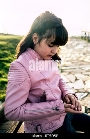 Girl wearing pink leather jacket looking at pebble in her hand - Stock Photo