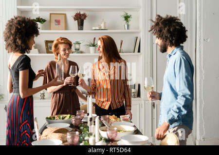 Freinds drinking wine at a dinner party, clinking glasses - Stock Photo