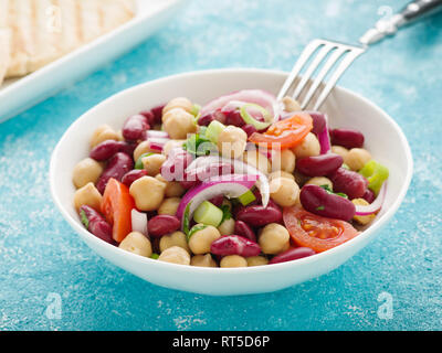 Tasty bean salad with chick peas, kidney beans and tomatoes. - Stock Photo