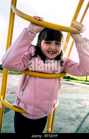 Portrait of girl with tooth gap wearing pink leather jacket on playground - Stock Photo