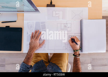 Close-up of architect working at home on floor plan - Stock Photo