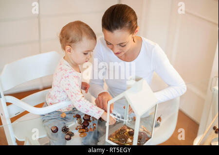 Mother and little daughter tinkering autumnal decorative house at home - Stock Photo