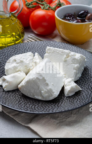 Fresh young soft white salted Feta cheese on black plate - Stock Photo