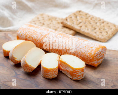 Fagotin cheese with  orange coloured rind made from cow milk in caves of Maredsous abbey, Belgium close up - Stock Photo