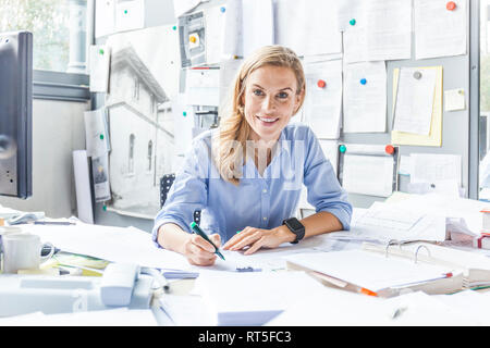 Portrait of smiling woman doing paperwork at desk in office - Stock Photo