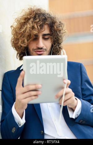 Portrait of young businessman using digital tablet outdoors