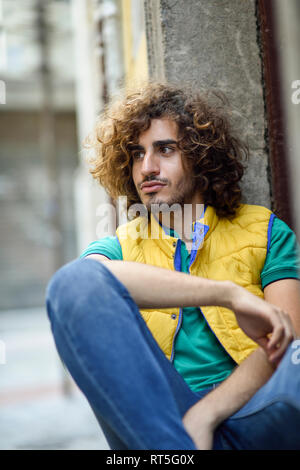 Portrait of young man with beard and curly hair wearing yellow waistcoat watching something - Stock Photo