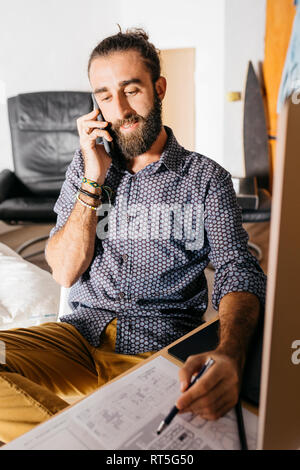 Young architect working at home with blueprints while talking on the phone - Stock Photo