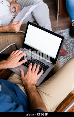 Close-up of businessmen with laptop and documents sitting in armchairs - Stock Photo