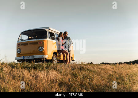 Young couple leaning on their camper, watching ghe sunset
