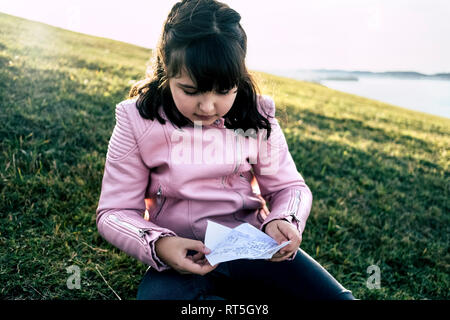 Portrait of girl wearing pink leather jacket sitting on a meadow looking at labelled paper - Stock Photo