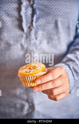 Woman's hand holding muffin with candied orange slice, close-up - Stock Photo