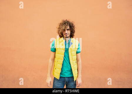 Portrait of annoyed young man with curly hair wearing yellow waistcoat outdoors - Stock Photo