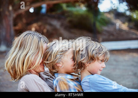 Happy mother with two sons sitting in a row outdoors - Stock Photo